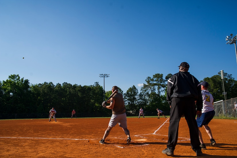 A 628th Security Forces Squadron player drives a ball up the middle during the 2013 Intramural Softball Season Opener May 14, 2013, at Joint Base Charleston – Air Base, S.C. The 437th Aircraft Maintenance Squadron team defeated the 628th SFS 15 – 7. (U.S. Air Force photo/Senior Airman George Goslin)