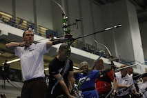 Archers in six different colored uniforms, representing  the six different wounded, ill and injured teams, prepare to fire a volley of arrows during the 2013 Warrior Games in Colorado Springs, Colo. This year all of the teams archery coaches were United States Marines.