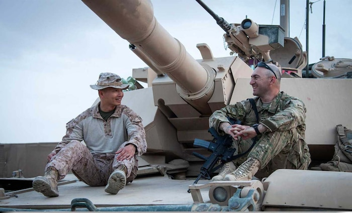 U.S. Marine Corps Master Sgt. Robert Oak, left, Civil Affairs operations chief, Headquarters Company, Regimental Combat Team 7, and Georgian Army Capt. Mikheil Mazmishvili, tour a M1A1 Abrams tank on forward operating base Shir Ghazay, Helmand province, Afghanistan, April 25, 2013.