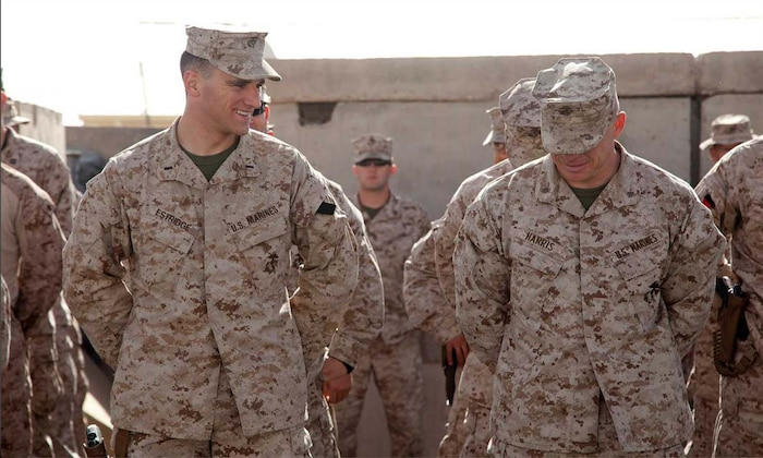 U.S. Marine Corps 1st Lt. Peter Estridge and Maj. Paul Harris, both assigned to Headquarters Company, Regimental Combat Team 7 share a moment of levity while waiting in formation on Camp Leatherneck, Helmand province, Afghanistan, May 1, 2013.