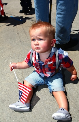 """Hunter Running, 11 months old, plays with an American flag while his family awaits the return of his father during a homecoming ceremony aboard Marine Corps Air Station Camp Pendleton, Calif., May 13. During their deployment with the 15th Marine Expeditionary Unit, the Marine Medium Helicopter Squadron 364 """"Purple Foxes"""" provided aerial support to the unit as the air combat element for the duration of the eight-month deployment."""