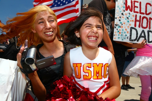 """Rosie Herrera, left, and Precious, right, her 9-year-old daughter, can't stop smiling during a homecoming ceremony aboard Marine Corps Air Station Camp Pendleton, Calif., May 13. Rosie's husband's deployment with Marine Medium Helicopter Squadron 364 """"Purple Foxes"""", 15th Marine Expeditionary Unit, represented the last deployment of Marine Corps CH-46 Sea Knight helicopters."""