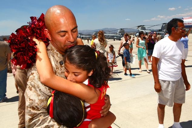 """Staff Sgt. Natividad Herrera, a helicopter mechanic with Marine Medium Helicopter Squadron 364 """"Purple Foxes,"""" holds his daughters for the first time in eight months during a homecoming ceremony aboard Marine Corps Air Station Camp Pendleton, Calif., May 13. While deployed with the 15th Marine Expeditionary Unit, his squadron provided round-the-clock aerial support to multiple missions all over the world."""