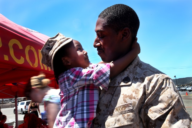 Petty Officer 3rd Class Roderick Shanks, a corpsman with Combat Logistics Battalion 15, 1st Marine Logistics Group, holds his daughter during CLB-15's homecoming aboard Camp Pendleton, Calif., May 13, 2013. Several Marines and sailors returned from an eight-month deployment with the 15th Marine Expeditionary Unit.