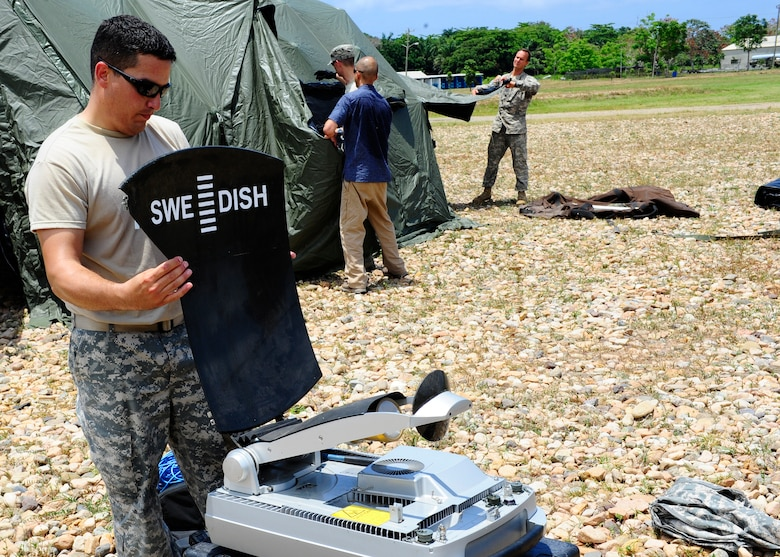 United States Army Staff Sgt. Frank Morales, CENTAM Survey and Assessment Team member, assembles a communication dish during a simulated Hurricane disaster response exercise at Puerto Castilla Honduras, May 15. The C-SAT team responds to a natural disaster and humanitarian assistance notification in the Central America Region to conduct an assessment of the area before military forces are deployed. (Air Force photo by Staff Sgt. Eric Donner)