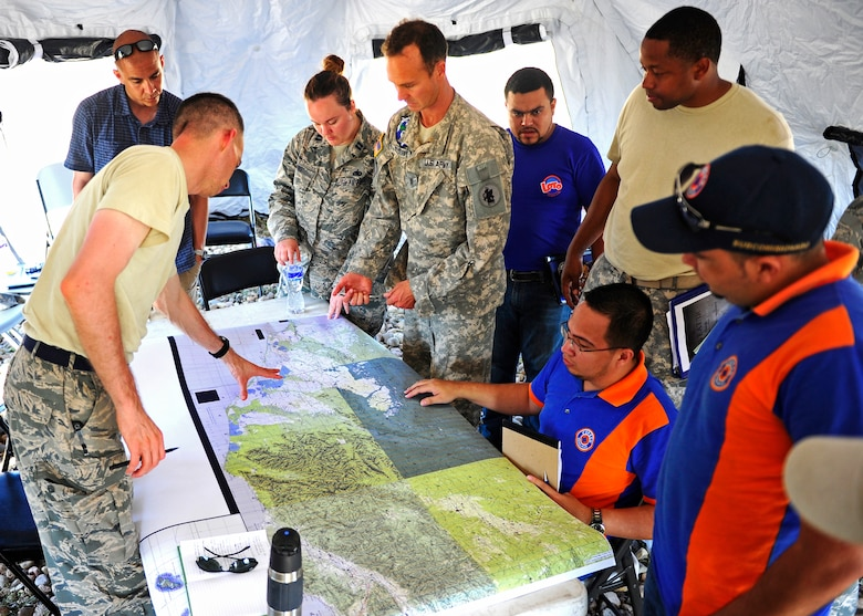 The CENTAM Survey and Assessment Team and the Honduran Comision Permanente de Contingencias look over a map of the affected area during a simulated hurricane disaster response exercise at Puerto Castilla, Honduras, May 15. The C-SAT team responds to a natural disaster and humanitarian assistance notification in the Central America Region to conduct an assessment of the area before military forces are deployed.(Air Force photo by Staff Sgt. Eric Donner)