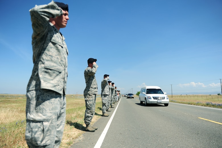 Defenders from the 9th Security Forces Squadron salute the procession of Staff Sgt. Richard Dickson during a dignified transfer at Beale Air Force Base Calif., May 10, 2013. Dickson was killed in a MC-12 Liberty aircraft crash in Afghanistan, April 27. (U.S. Air Force photo by Robert Scott/Released)