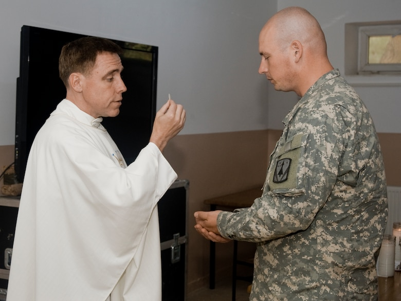 Chaplain Maj. Robert Monagle, 39th Air Base Wing Catholic chaplain, hands a piece of sacramental bread representing the body of Christ to U.S. Army Spc. Christopher Memmel, 3rd Battalion, 2nd Air Defense Artillery deployed from Fort Sill, Okla., April 14, 2013 at Gaziantep, Turkey. The soldiers from the 3-2 ADA are deployed to augment Turkey's air defense capabilities and contribute to the de-escalation of the crisis along the country's Syrian border. (U.S. Air Force photo by Staff Sgt. Eric Summers Jr./Released.)