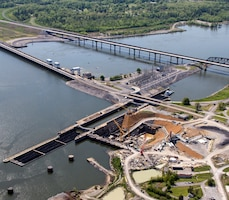 This aerial photo of the Kentucky Lock Addition project taken April 26, 2013 in Grand Rivers, Ky., shows construction of a new 1200-foot lock landward of the existing 600-foot lock and the relocated highway and railroad bridges downstream of the dam. The upstream-bound split barge tow will be able to lock through as a single tow when the new lock is completed by the U.S. Army Corps of Engineers Nashville District in partnership with the Tennessee Valley Authority.
