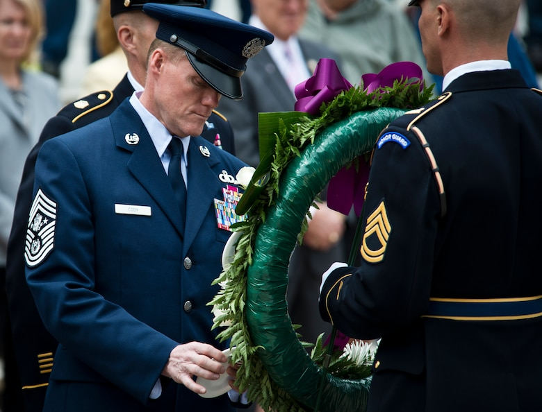 Chief Master Sgt. of the Air Force James A. Cody places a service crest on a wreath in honor of Airmen's sacrifices during the inaugural Armed Forces Day wreath-laying ceremony May 18, 2013, at the Tomb of the Unknown Soldier at Arlington National Cemetery, Va. Cody along with the senior enlisted advisers from the Army, Navy, Marine Corps,and Coast Guard hung logos of their service on a wreath wrapped with purple ribbon just steps away from the gravesite. (U.S. Air Force photo/Senior Airman Andrew Lee)