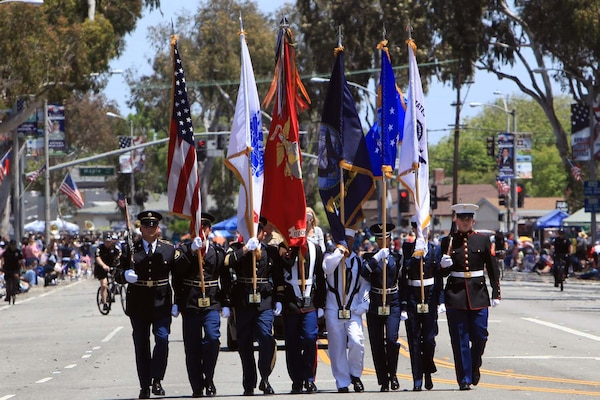 Image of military members carrying flags during a parade.