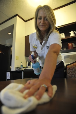 Melissa Bailey, 509th Force Support Squadron housekeeper, cleans furniture at the Whiteman Inn on 