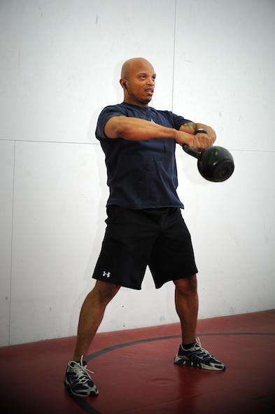 U.S. Air Force Master Sgt. Claude Lawson, 27th Special Operations Force Support Squadron military personnel flight superintendent, demonstrates kettle bell swing at Cannon Air Force Base, N.M., May 18, 2013.  Certified as a personal trainer, Lawson uses his Mixed Martial Arts background to coach new fighters.  (U.S. Air Force photo/Senior Airman Jette Carr)