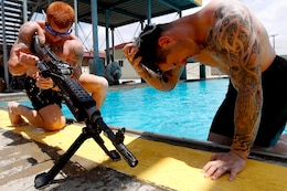 Sgt. Johnathan Bumpus performs a functions check on an M2-40G machinegun that he and his teammate, Sgt. Alexander Hale, assembled under 15-feet of water during the 5th Annual Recon Challenge here May 17. The challenge consisted of a 2,000-meter swim, calisthenics tests and other skill based events.