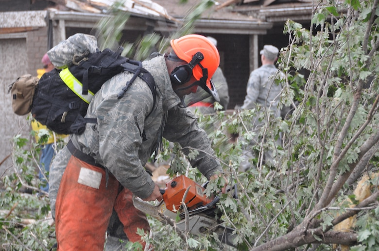 A military member cuts trees that were brought down on homes after a tornado hit the town of Moore, Okla. May 20, 2013.  (U.S. Air Force photo by Maj. Jon Quinlan)