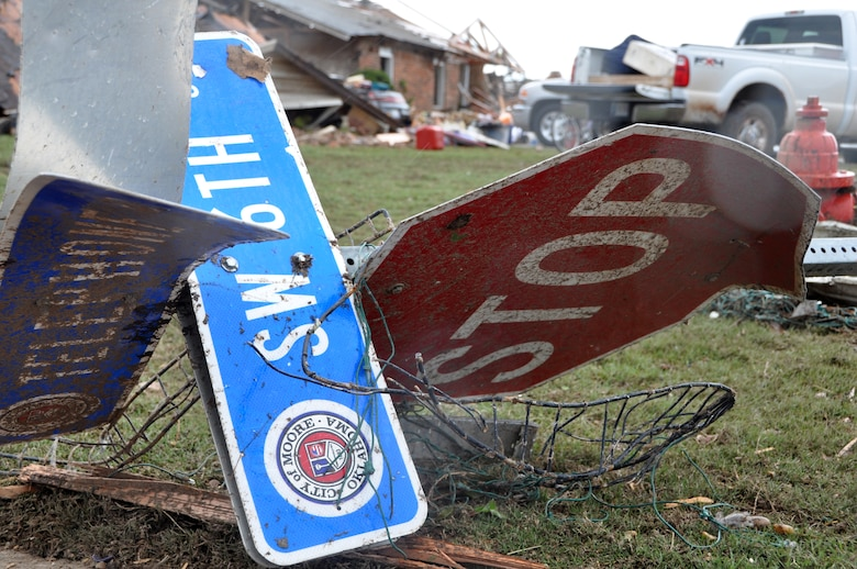 A twisted up sign from SW 6th and Telephone Road landed in the front yard of 137th Air Refueling Wing Oklahoma Air National Guard member, Master Sgt. Cherry Bina.  Bina's house was destroyed during the massive tornado that ripped through Moore Okla., on May 20, 2013.  (U.S. Air Force photo by Senior Airman Mark Hybers)