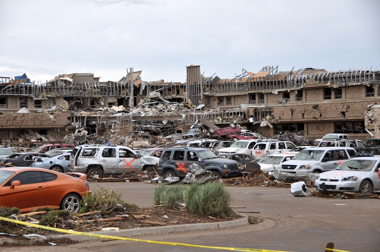 The Moore Medical Center – Norman Regional Hospital in Moore Okla., is ripped apart by the massive tornado on May 20, 2013.  The hospital was directly in the path of the 1.3 mile wide tornado that hit Moore in the late afternoon.  There were no casualties reported.  Cars flipped over and piled on top of one another along with cars that were cleared away by first responders fill the parking lot.  The Orange X spray painted on the cars indicates that the vehicle was checked and cleared of any victims.  (U.S. Air Force photo by Senior Airman Mark Hybers)