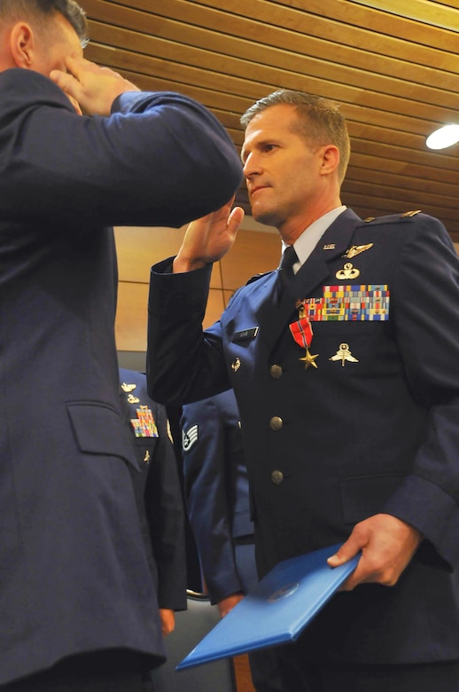 JOINT BASE ELMENDORF-RICHARDSON, Alaska -- Capt. Christopher Keen, a pararescueman from the 212 Rescue Squadron, salutes his commander, Maj. Joseph Conroy, after recieving a Bronze Star Medal. One Silver Star Medal and six Bronze Star Medals were handed out here May 18 to men of valor from the Alaska Air National Guard's 212 Rescue Squadron. The medals were presented for actions from the 212 Rescue Squadron's deployments in 2011 and 2012.  National Guard photo by Staff Sgt. N. Alicia Goldberger.