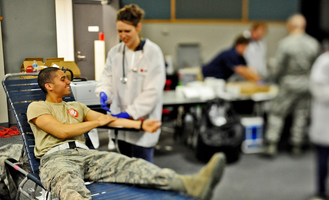 Airman 1st Class Randolph Baez, 509th Civil Engineer Squadron blood donor, shares a laugh with Deb Stewart, American Red Cross collection technician, as she processes his blood at an American Red Cross blood drive at Whiteman Air Force Base, Mo., May 16, 2013. The American Red Cross supplies more than 40 percent of America's blood supply and provides blood for patients in more than 3,000 hospitals across the U.S. (U.S. Air Force photo by Staff Sgt. Nick Wilson/Released)