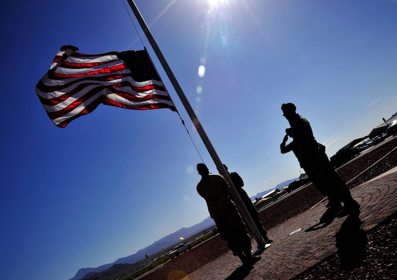 LAS VEGAS, Nev. -- Airmen from the 799th Security Forces Squadron lower the U.S. flag during a formal retreat ceremony, May 15, 2013. The ceremony, which was part of National Police Week, took place to honor fallen security forces Airmen and other law enforcement members who have paid the ultimate sacrifice to ensure the nation's safety. (U.S. Air Force photo by Staff Sgt. A.D./Released)