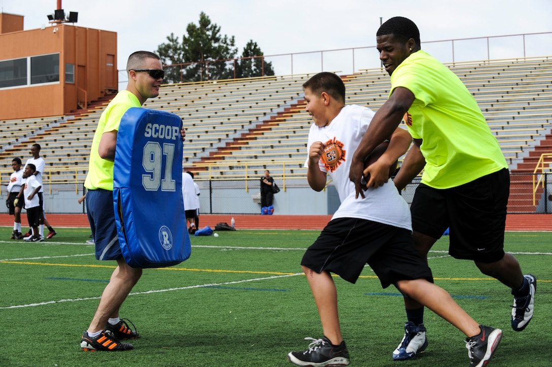 Timothy Barnhart, left, anticipates a hit from a 16Ways football camp participant as Maurice Greer, right, attempts to fumble the ball May 18, 2013, at the Aurora Public Stadium, Aurora, Colo. Barnhart, an Air Force staff sergeant with the 460th Medical Group, was one of about 30 volunteers from Buckley Air Force Base to participate in the camp, which focused on basic football fundamentals, teamwork and anti-bullying. (U.S. Air Force photo by Staff Sgt. Christopher Gross/Released)