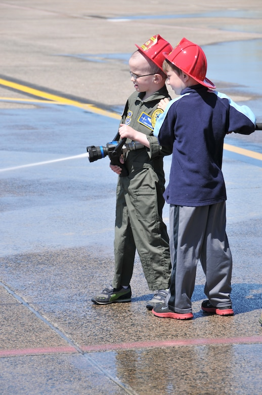 Logan Schoenhardt and his friend, Andrew Kerwin,  spray the fire hose on the ramp at Bradley as they pretend to be military firefighters during the Pilot for A Day Program at Bradley Air National Guard Base, East Granby, Conn., May 3, 2013. (Air National Guard photo by Senior Airman Jennifer Pierce/Released)