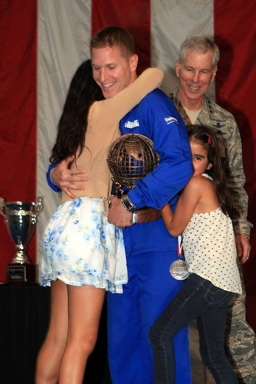 """Capt. Mitchell Kieffer, an operations research analyst from Joint Base Langley-Eustis, Va., accepts the """"Ultimate Champion"""" award with his daughters, Ana Paula and Ana Christina, at the 2013 Warrior Games in Colorado Springs, Colo., May 16, 2013. He became the first Air Force athlete in Warrior Games history to earn the title, taking first place in the five-event competitive track-and-field crucible. (Courtesty photo/Released)"""