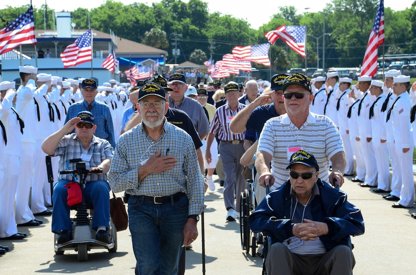 Surviving crewmembers of the USS Franklin (CV 13) walk toward the USS Yorktown (CV 10) for their final reunion May 17, 2013, at Patriots Point Naval and Maritime Museum in Mt. Pleasant, S.C. On March 19, 1945, the Franklin was hit by two Japanese bombs, which ignited armed aircraft and triggered a gasoline vapor explosion devastating the hangar bay, killing more than 800 Sailors and wounding nearly 500. (U.S. Air Force photo/Staff Sgt. Anthony Hyatt)