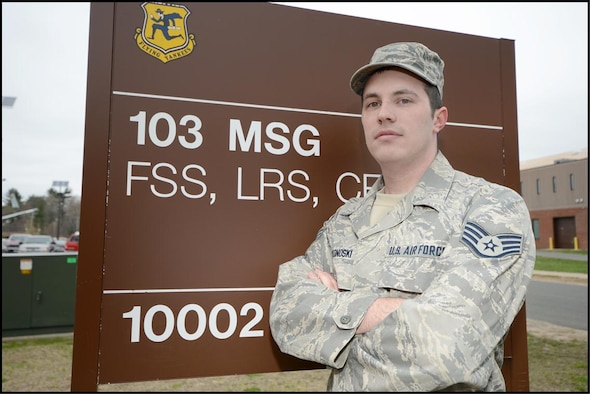 Staff Sgt. Dustin Wonoski, a member of the 103rd Logistics Readiness Squadron, stands in front of a building sign at Bradley Air National Guard Base, East Granby, Conn. Wonoski put service before self on April 15, 2013, when he found himself in the middle of the Boston Bombing. (Air National Guard photo by Tech. Sgt. Joshua Mead/Released)