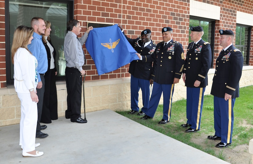 Leaders from the 128th Aviation Brigade and members of retired U.S. Army Command Sgt. Maj. Richard Lee Jackson's family unveil a plaque during the dedication of Jackson Hall at Fort Eustis, Va., May 21, 2013. The brigade dedicated the first of several  forthcoming Soldier barracks in Jackson's honor for his service to the U.S. Army Transportation and Aviation Logistics School, and later, the U.S. Army Aviation Logistics School, the brigade's predecessor. (U.S. Air Force photo by Tech. Sgt. April Wickes/Released)