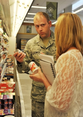 Staff Sgt. Brett Lodwick, 509th Munitions Squadron munitions systems craftsman, listens as Valerie Rogers, 509th Medical Operations Squadron community dietitian, explains the different ingredients in similar products during a commissary tour at Whiteman Air Force Base, Mo., May 10, 2013. Commissary tours are given once a month by a HAWC dietitian and provide a unique opportunity to help change buying habits. (U.S. Air Force photo by Heidi Hunt/Released)