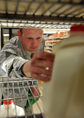 Staff Sgt. Brett Lodwick, 509th Munitions Squadron munitions systems craftsman, reaches for a gallon of milk to compare ingredients during a commissary tour at Whiteman Air Force Base, Mo., May 10, 2013. The Health and Wellness Center provides monthly tours of the commissary to familiarize Team Whiteman with the nutritional value of groceries they choices. (U.S. Air Force photo by Heidi Hunt/Released)