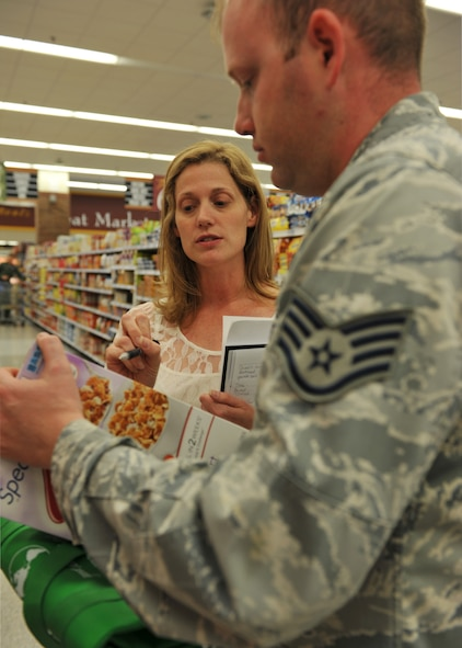 Valerie Rogers, 509th Medical Operations Squadron Health community dietitian, interprets a label on a box of cereal for Staff Sgt. Brett Lodwick, 509th Munitions Squadron munitions systems craftsman, during a tour of the commissary at Whiteman Air Force Base, Mo., May 10, 2013. The purpose of these tours is to provide Airmen and their families the chance to ask specific questions tailored to their health and nutrition needs and get acquainted with healthier options when grocery shopping. (U.S. Air Force photo by Heidi Hunt/Released)