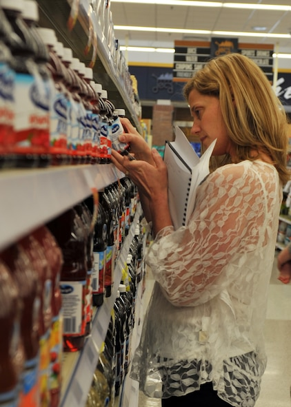 Valerie Rogers, 509th Medical Operations Squadron community dietitian, looks at the nutrition label on a bottle of juice during a tour of the commissary at Whiteman Air Force Base, Mo., May 10, 2013. Rogers discussed the names of hidden sugars and told participants what to look for when shopping for healthier foods. (U.S. Air Force photo by Heidi Hunt/Released)