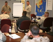 Marine Maj. Shawn Rickrode (right), the future operations officer at Marine Corps Security Cooperation Group guides students of the Marine Corps Command and Staff College on how to implement Security Cooperation into Campaign and Support Planning during Exercise Nine Innings. This exercise is the college's capstone planning exercise. It requires the more than 200 U.S. and international field grade officers and interagency civilian students to think critically about complex regional security challenges. Marine Corps Security Cooperation Group executes and enables Security Cooperation (SC) programs, training, planning, and activities in coordination with the operating forces and Marine Air-Ground Task Forces in order to ensure unity of effort in support of U.S. Marine Corps and regional Marine Forces (MARFOR) Component Command objectives.