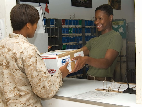 Sgt. Stephanie A. Bowens, postal clerk, Base Mailroom, Marine Corps Logistics Base Albany, hands a Marine a package. Bowens was meritoriously promoted to the rank of sergeant during a ceremony held in front of Building 3500, here, May 13.