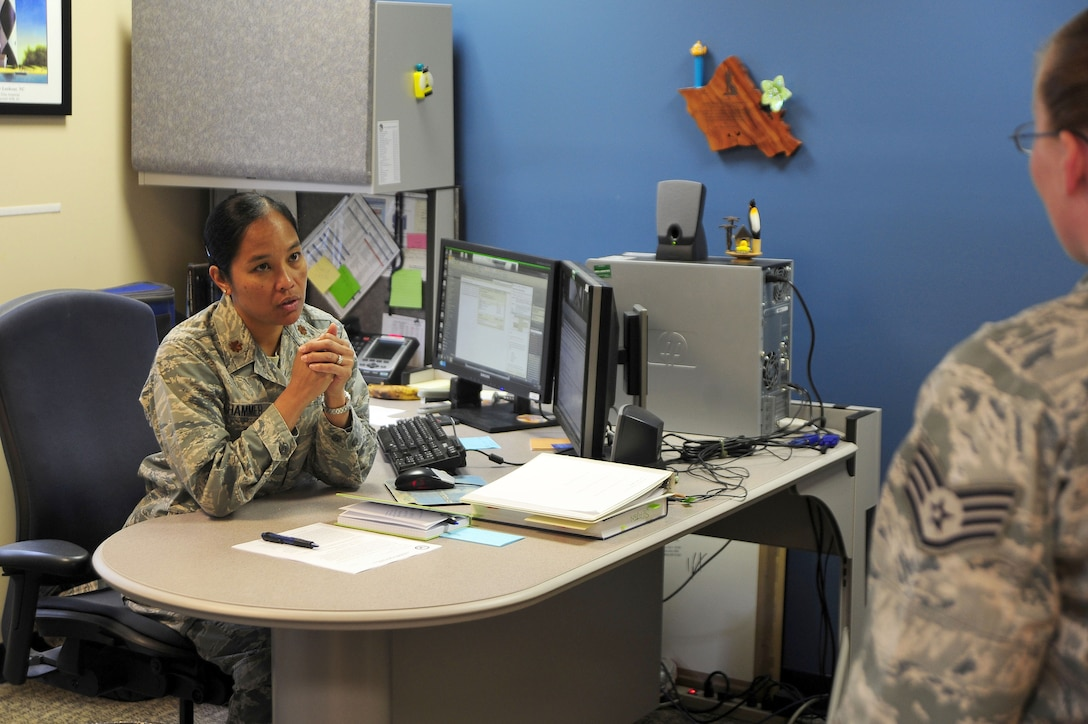 Maj. Elisa Hammer, 779th Aeromedical Squadron Bioenvironmental Engineering Flight chief, speaks with an Airman in her office, May 2, 2013, at Joint Base Andrews, Md. As the flight chief, Hammer?s job is to enforce worker protection against occupational health hazards, such as chemical, biological, radiological, nuclear and physical threats at JBA. (U.S. Air Force photos by Senior Airman Steele C. G. Britton)