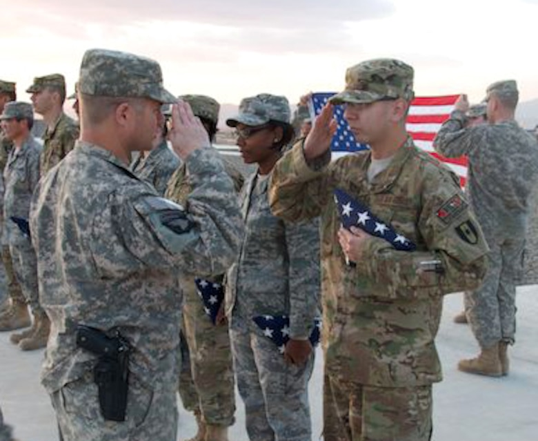 U.S. Air Force Senior Airman Zachariah Gray, 366th Aerospace Medical technician, receives a flag from his commander during a ceremony at his deployed location in Afghanistan. Gray has deployed twice, each time earning valuable medical experience in the process.  (U.S. Army photo by Sgt. Kyle B. Carpenter/Released)