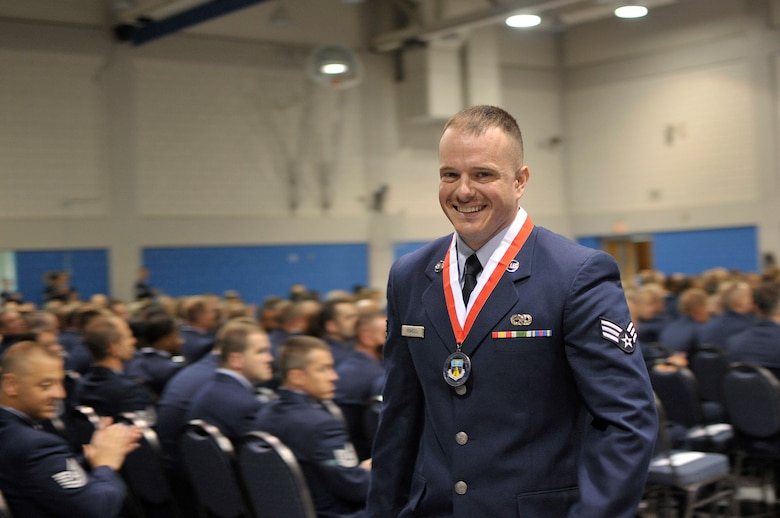 """MCGHEE TYSON AIR NATIONAL GUARD BASE, Tenn. – U.S. Air National Guard Senior Airman Victor Popescu, from Ohio, is called to the stage for earning the Academic Achievement Award for Airman Leadership School. Popescu graduated with others from his ALS class as well as Noncommissioned Officer Academy graduates May 23, 2013, from the Paul H. Lankford Enlisted Professional Military Education Center. Their ceremony featured guest speaker Chief Master Sgt. Richard A. """"Andy"""" Kaiser, command chief of U.S. Air Force Air Mobility Command. (U.S. Air National Guard photo by Master Sgt. Mike R. Smith/Released)"""