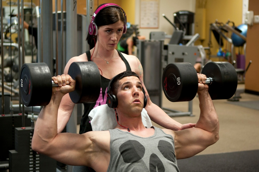Holly Watters helps her husband Michael, do a seated dumbbell press during a workout at Anytime Fitness gym in Bossier City, La., May 15, 2013. Holly is a crew chief and Air Reserve Technician (ART) assigned to the 917th Maintenance squadron as well as a National Physique Committee (NPC) National Level Figure Competitor, who is in training for The Louisiana State Championships in Lafayette this July. (U.S. Air Force photo by Master Sgt. Jeff Walston)