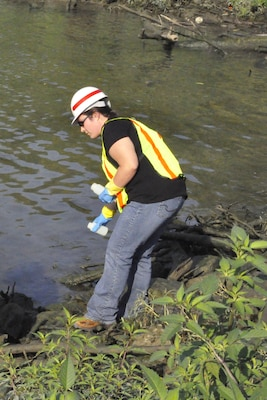 Jade Young, Louisville District, U.S. Army Corps of Engineers biologist, gathers samples for testing water quality.