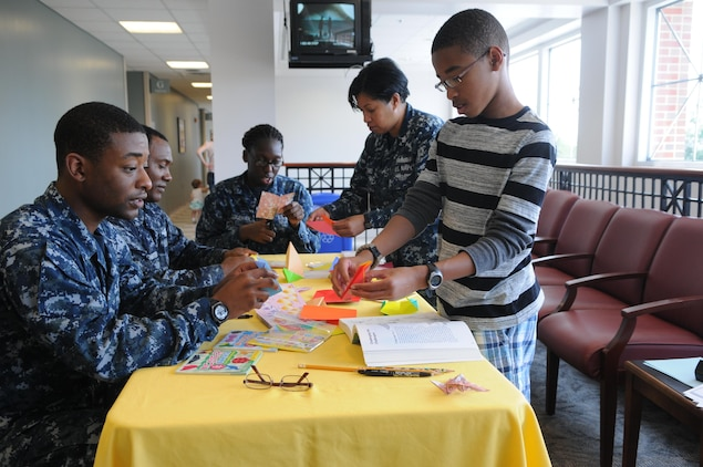 From left, Seaman Keith Collier, Petty Officer 2nd Class Neil Chichester and Seaman Erica Coleman get an origami lesson from Petty Officer 1st Class Arlene Jones and her 13-year-old son Emmanuel during Naval Health Clinic Quantico's Asian-Pacific American Heritage Month celebration May 22, 2013.