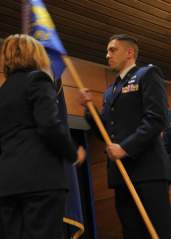 """JOINT BASE ELMENDORF-RICHARDSON -- Lt. Col. Keolani """"K O"""" Bailey accepts the 176 Logistics Readiness Squadron flag here May 18, 2013, from Col. Patty Wilbanks, commander of the 176 Misison Support Group, signifying he assumed command of the squadron. National Guard photo by Staff Sgt. N. Alicia Goldberger."""