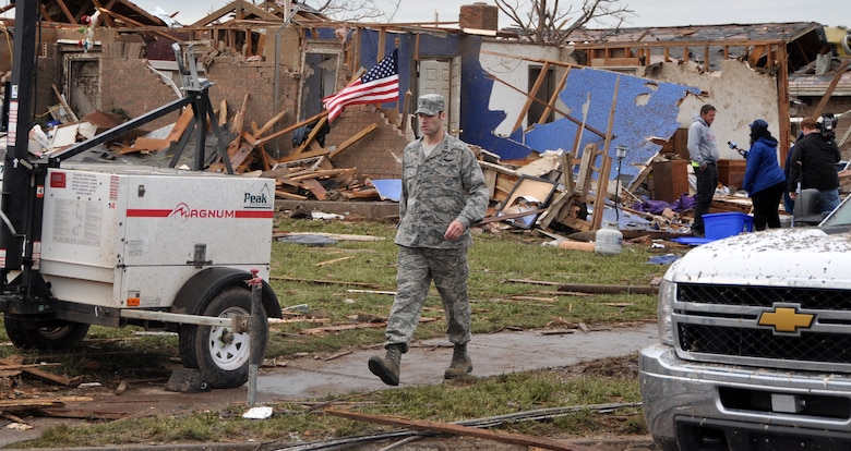An Air Force member moves through a neighborhood looking for people in need of help in the aftermath of the devastating tornado that ripped through Moore Okla., Monday May 20, 2013.  One of the hundreds of Oklahomans to lose their homes is being interviewed as the Airman watches for downed power lines and debris.  (U.S. Air Force photo by Senior Airman Mark Hybers)