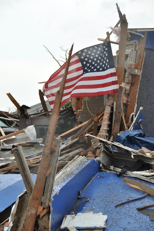 A United States flag flies from the ruble of a home destroyed in Moore, Okla. A powerful EF-5 tornado touched down approximately three miles south of Tinker AFB. (U.S. Air Force photo by Maj. Jon Quinlan)