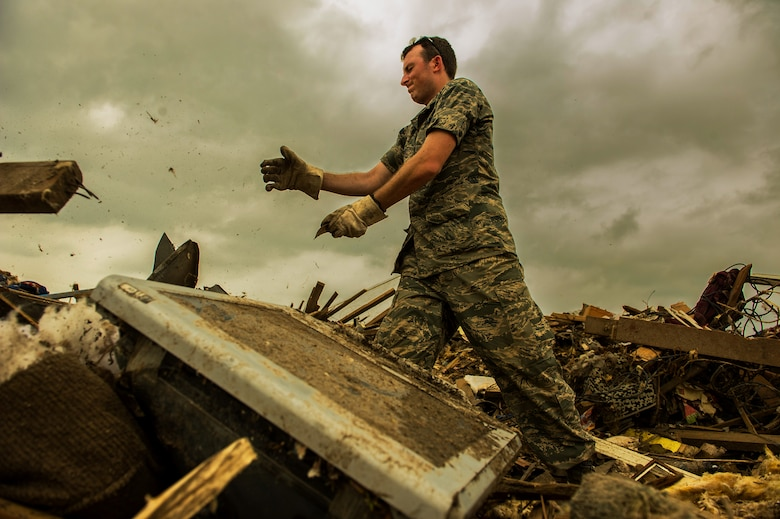 U.S. Air Force Capt. Ryan Gers, searches through the rubble of a leveled home, May 23, 2013, looking for anything salvageable after a tornado ripped through parts of Moore, Okla., May 20, which damaged more than 13,000 homes. More than 600 Airmen from the greater Oklahoma area volunteered to assist in the relief efforts. Gers is assigned to the 965th Airborne Air Control Squadron, Tinker Air Force Base, Okla., and hails from Scottsdale, Ariz. (U.S. Air Force photo by Staff Sgt. Jonathan Snyder)
