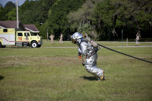A Crash Fire Rescue Marine with Marine Corps Air Station (MCAS) Beaufort Aircraft Rescue and Firefighting unit, prepares a hose to extinguish a fire during a training exercise on May 15, 2013.