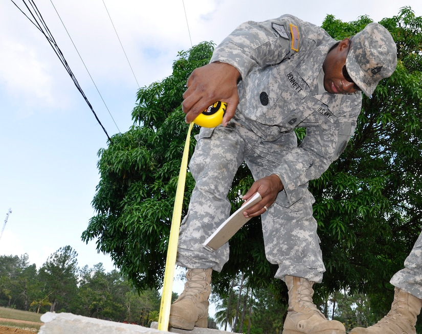 United States Army Master Sgt. Dunte Bennett Joint Task Force-Bravo Engineer Non-commissioned Officer in Charge measures the completed sewer system at the Honduran army base Mocoron, May 21. The team, led by Honduran military engineers, is conducting a topographical survey of the current infrastructure, to begin planning the next stage of facility upgrades. (U.S. Air Force photo by Staff Sgt. Eric Donner)