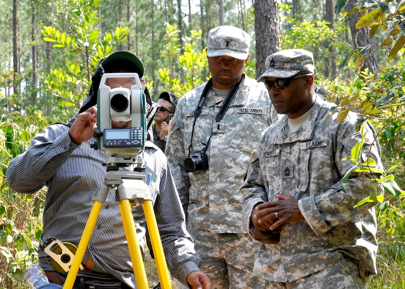 United States Army 1st Lt. Jonathan Logan, Joint Task Force-Bravo Engineer Project Officer, Master Sgt. Dunte Bennett, JTF-B Engineer Non-commissioned Officer in Charge assists a Honduran engineer surveying the fresh water source at the Honduran army base Mocoron, May 20. The team, led by Honduran military engineers, is conducting a topographical survey of the current infrastructure, to begin planning the next stage of facility upgrades. (U.S. Air Force photo by Staff Sgt. Eric Donner)