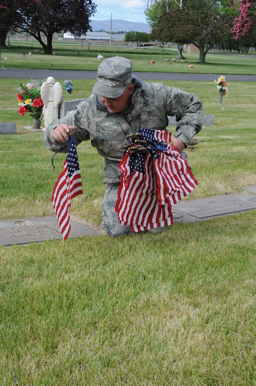 U.S. Air National Guard Master Sgt. Dave Smith, 173rd Fighter Wing, places a flag on the graves of local veterans at Mount Calvary Cemetery in Klamath Falls, Ore. May 23, 2013.  Members of the 173rd Fighter Wing spent their morning placing flags in honor of Memorial Day.  (U.S. Air National Guard photo by Master Sgt. Jennifer Shirar) RELEASED